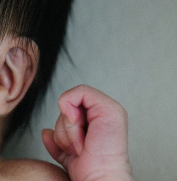 Baby with ear and hand