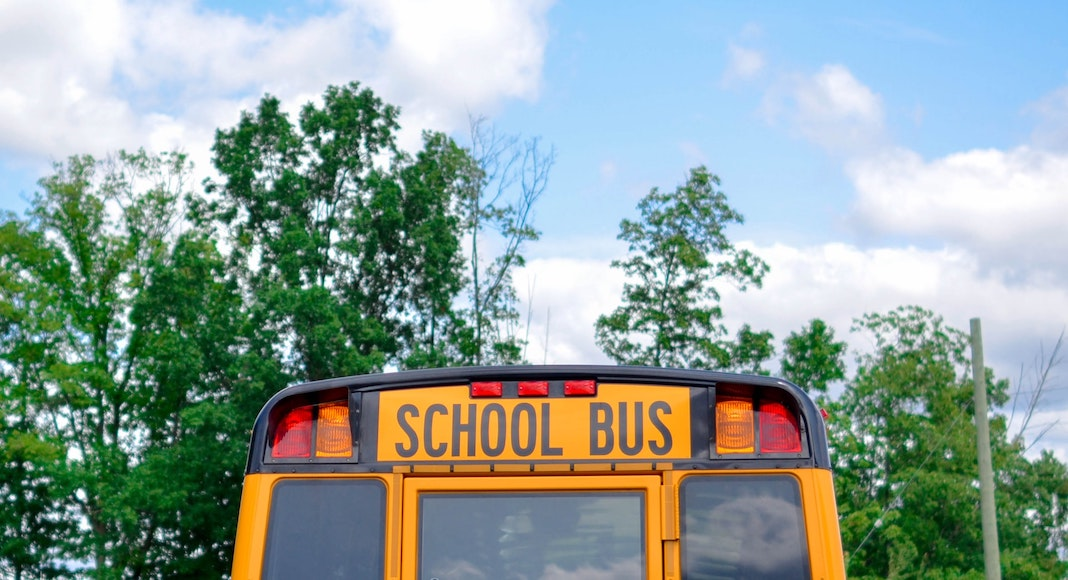 Yellow school bus against blue sky with clouds
