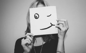 Woman holding up a smiling face over her own face