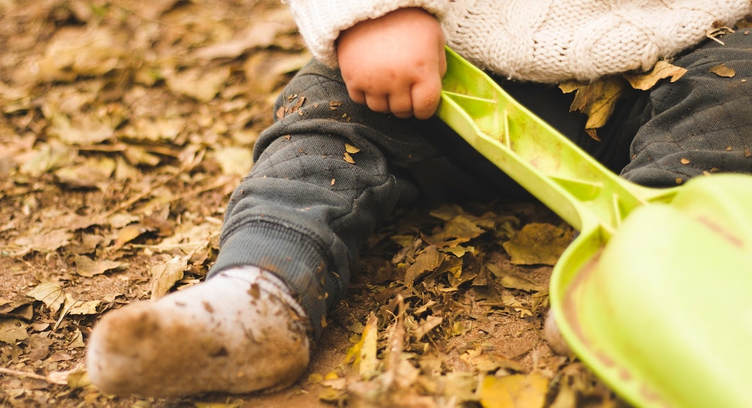 Baby with muddy socks sitting in autumn leaves
