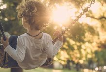 Child on swing with sun shining in background through trees