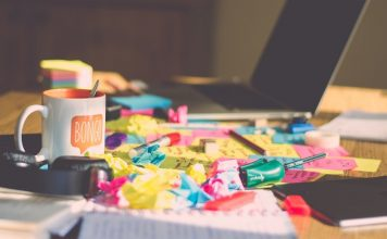 Mess of toys, paper coffee on desk