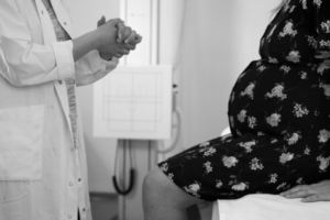 prenatal genetic testing image of pregnant woman speaking with a doctor