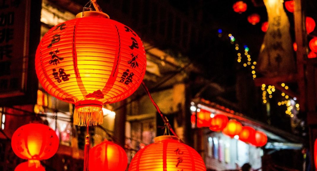 Image from Chinese New Year that has illuminated red lanterns hanging about a market place with Chinese characters painted on them