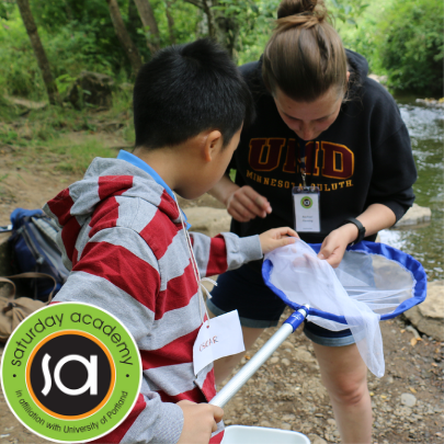 Image of Student and Counselor at Camp looking into a new at a river