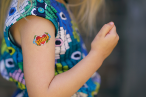 image of a young child showing off her bicep with a temporary tattoo of a heart with Mom in the middle