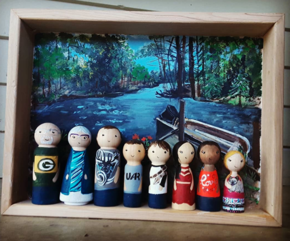 A Family of peg dolls in front of a painted river background from Sudie's Corner for a unique Mother's Day gift