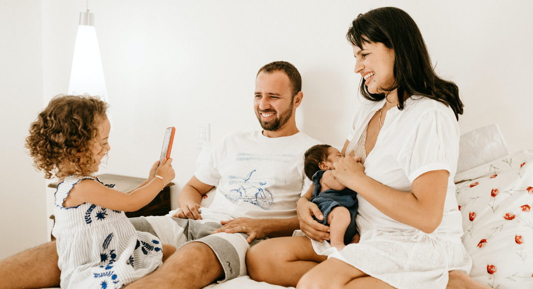 Two parents sitting together at home while their toddler takes a picture of them with a phone and the infant breastfeeds