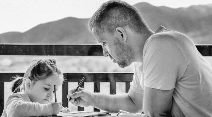 Father sitting at the table with his young child to color and talk
