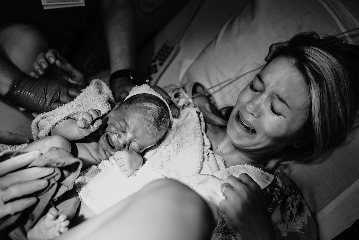 Mother who's just given birth is handed her baby while crying with emotion