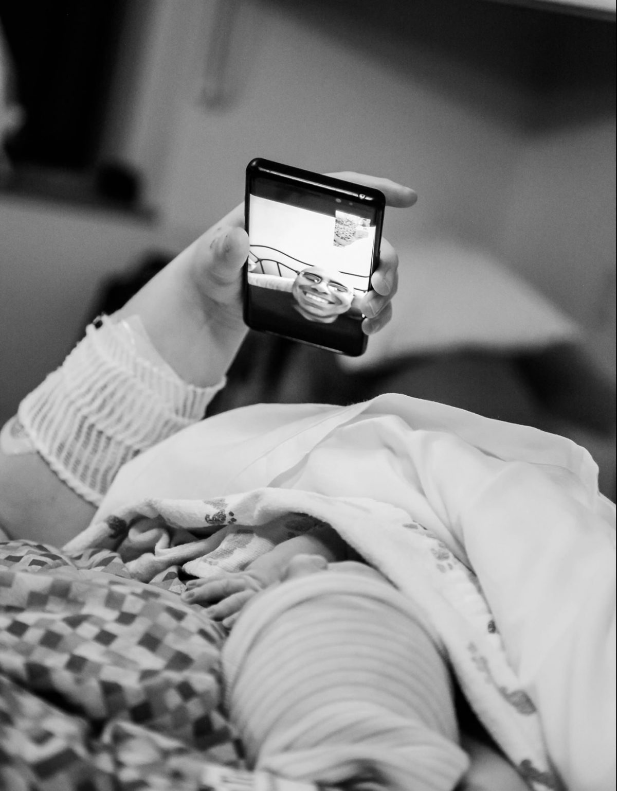 New moms lays newborn on her chest as she holds a cell phone in her other hand to video chat with baby's dad