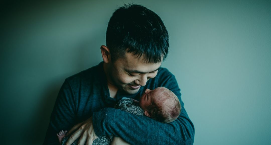 A father holding and staring at his newborn baby with a smile on his face in front of a teal background