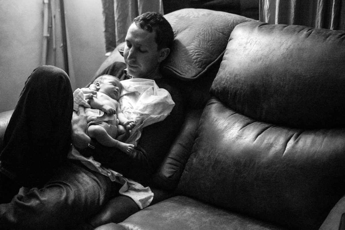 Father sitting on a couch holding and looking down at his infant son whom he has adopted that day from Serravision Photography