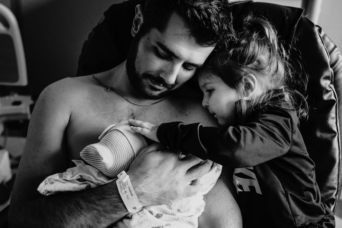 Man holding his newborn son skin-to-skin when his daughter looks at her new little brother from Portland Birth Photographer: Natalie Broder