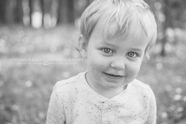 Close up black and white image with a child smiling by Studio Nagita Photography
