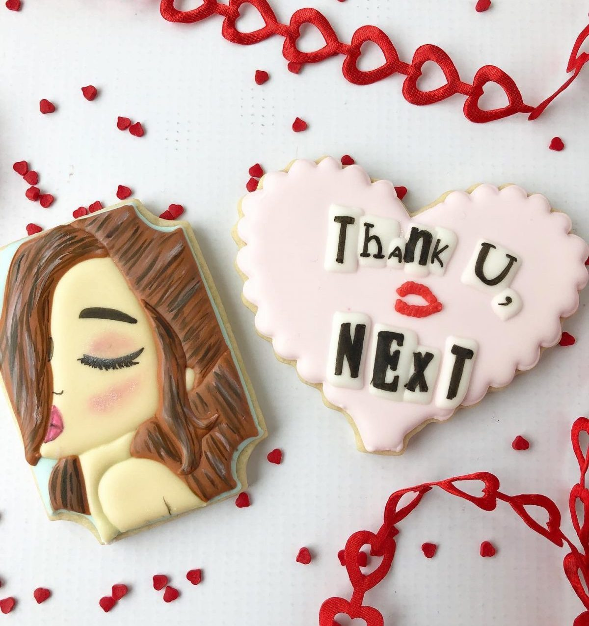 """Two cookies on a Valentine's Day background. One cookie is decorated to look like Arianna Grande and the other says, """"Thank U, Next"""""""