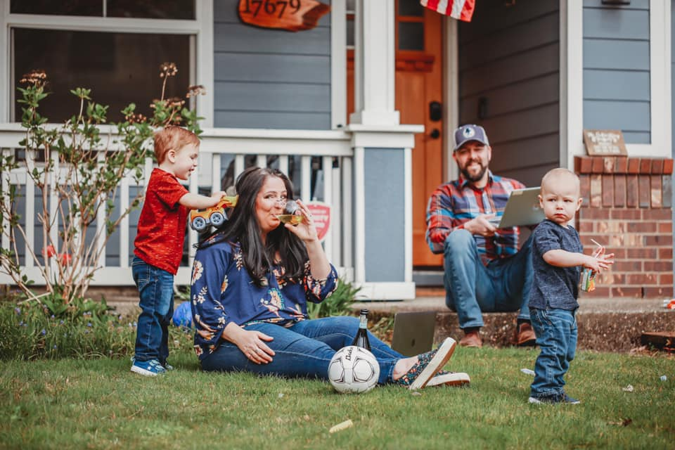 A Family in their front lawn with two parents and two children. The mom is sitting on the ground drinking wine while the dad is on his laptop and the two young children are running around by Chelletography