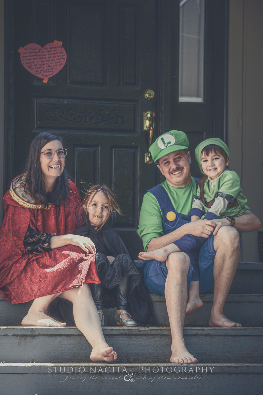 A family of four sitting together on their front steps dressed in various Halloween costumes to celebrate their daughter's 7th birthday (in April) by Studio Nagita Photography