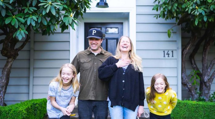 Kitta Bodmer Photography image of family of four standing in front of their home laughing together