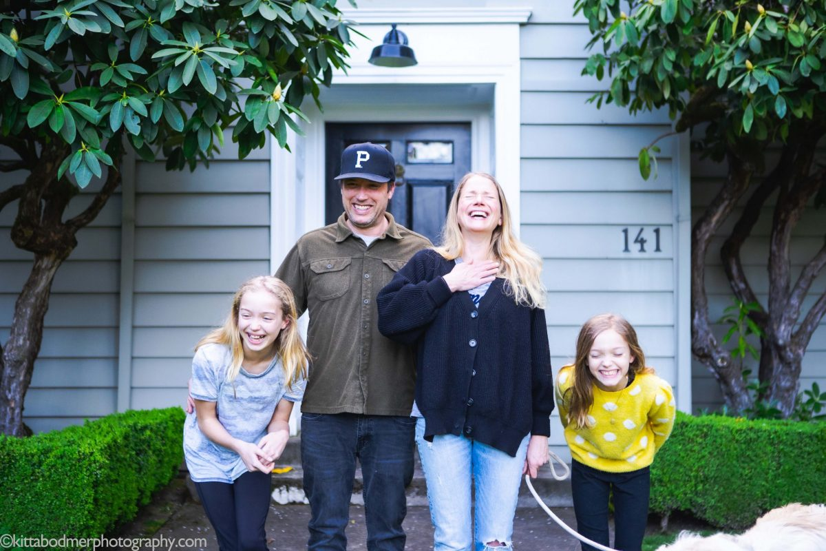 A dad, mom, and their two daughters laughing in front of their home by Kitta Bodmer Photography