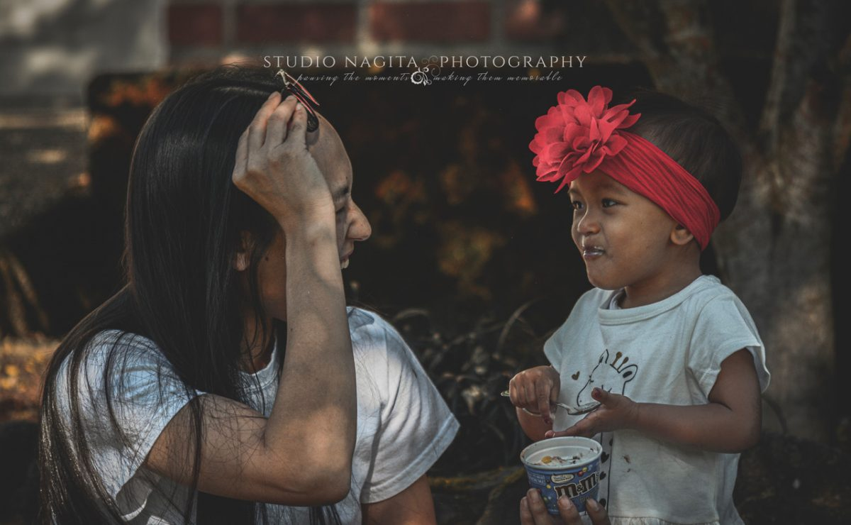 A mother looking at her young daughter eating ice cream and smiling from Studio Nagita Photography