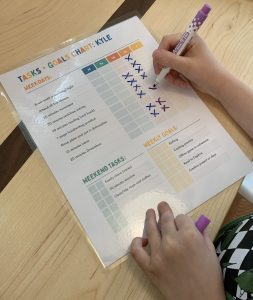 Kid filling out task chart