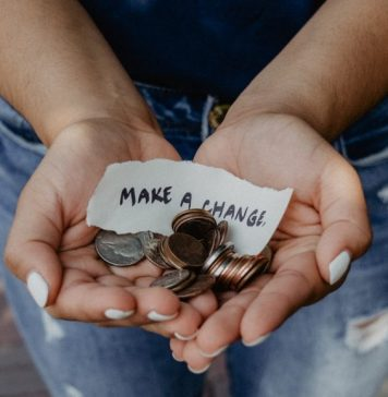 image depicting donations via a woman holding her hands out with coins and a piece of paper that says make a change