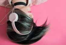 women with black and green hair covering her face laying down on a pink background with headphones on
