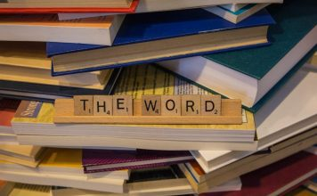 """Letter tiles spelling out """"THE WORD"""" on a pile of books"""