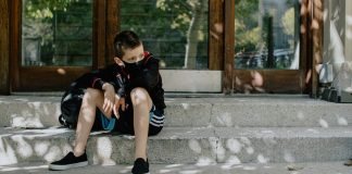 Kid sitting on steps outside of school