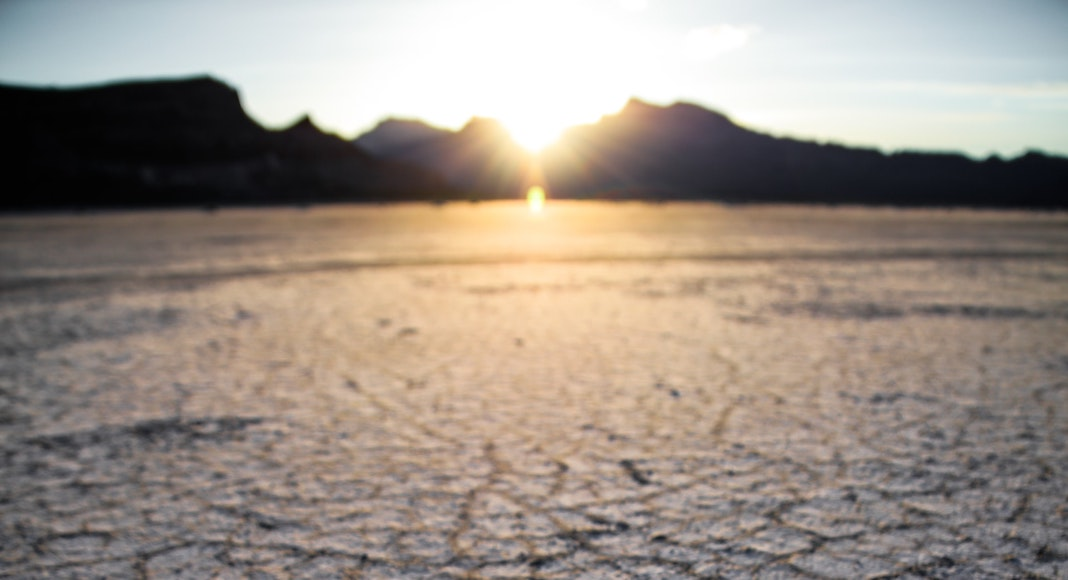Dry desert with sun behind mountains